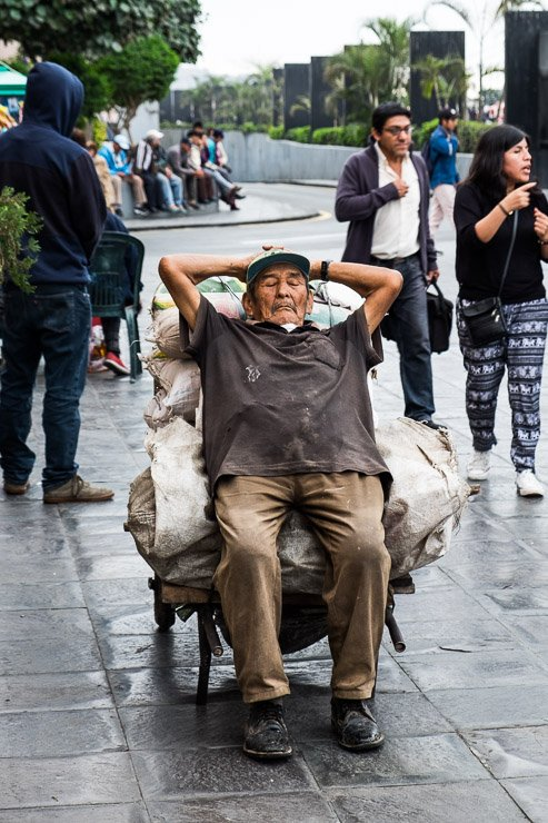 Man asleep resting against cart, Alameda Chabuca Granda, Lima