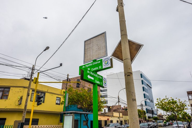 Signpost for Avenida Mariscal La Mar, Lima, with helicopter overhead