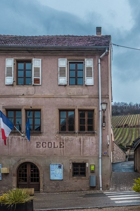 View from Catherine Riss's cave, Bernardville, Alsace, with French flag, school and vineyards