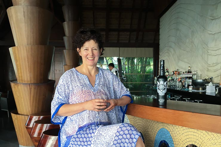 Gina Power sitting at the bar at Sugar Beach Resort, Mauritius, with glass of Pink Pigeon rum