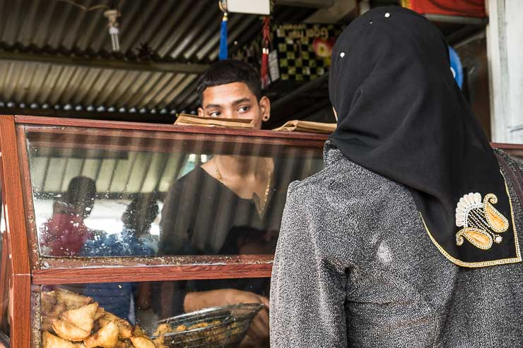 Man selling samosas looking at woman with headscarf, Quatre Bornes market, Mauritius