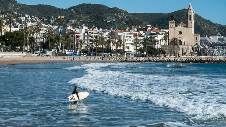 Surfer at beach, Sitges, with San Sebastian church behind