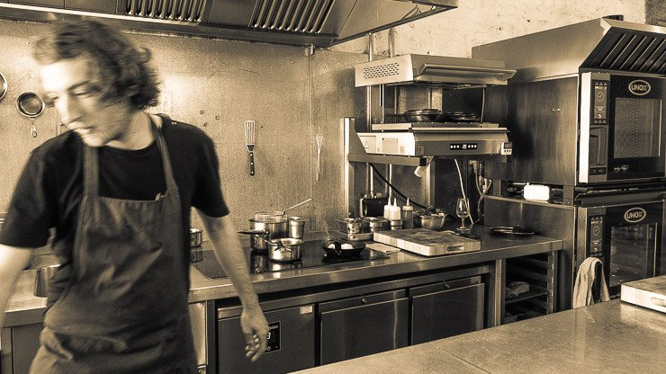 View of the kitchen from the bar, with chef, Silo Restaurant, Brighton