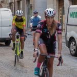 3 cyclists in lycra riding through old city of Girona