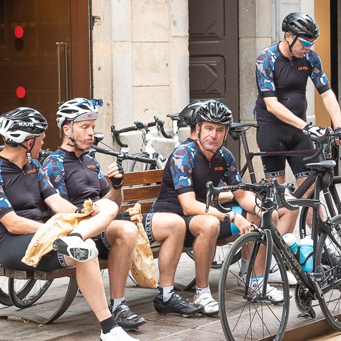 Cyclists sitting down and eating outside Casa Moner, Girona