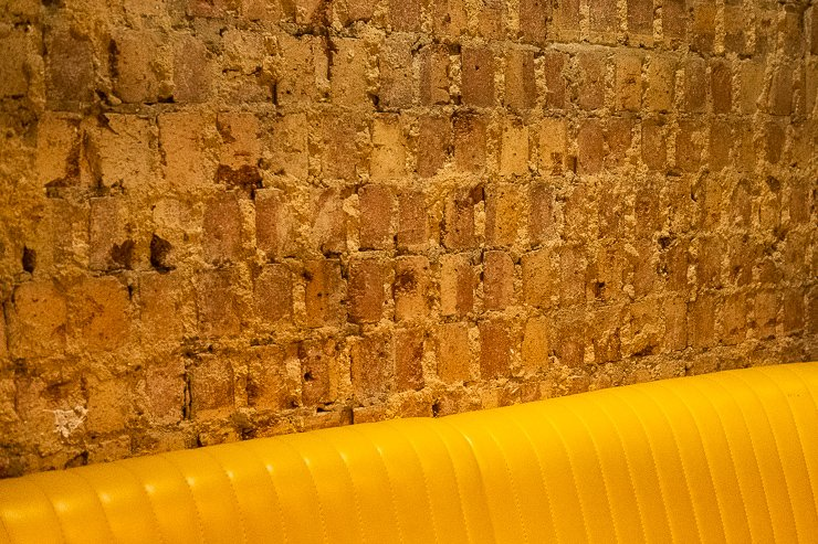 yellow seat and brick wall,Lyan Cub, Hoxton, London