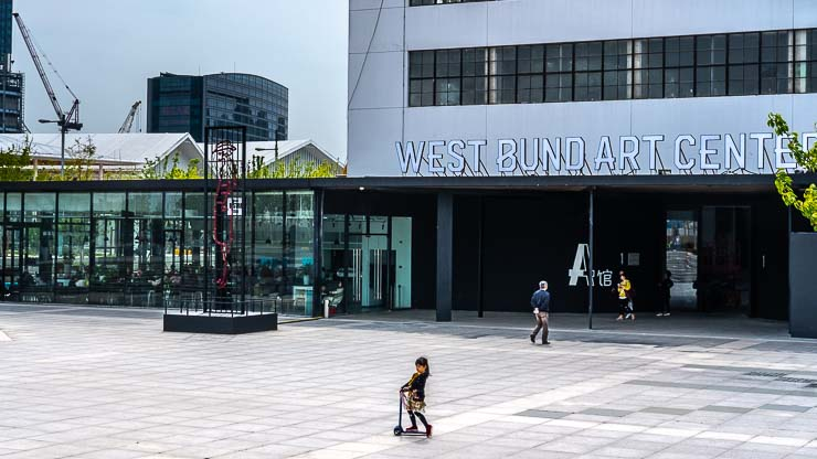 West Bund Art Centre, Shanghai, with girl going past on a scooter