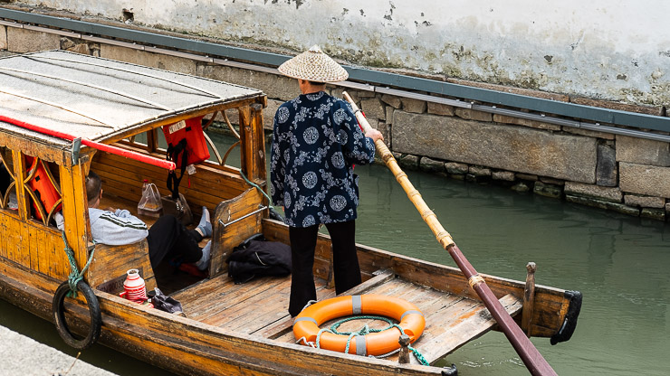 Man steering boat on canal, Suzhou