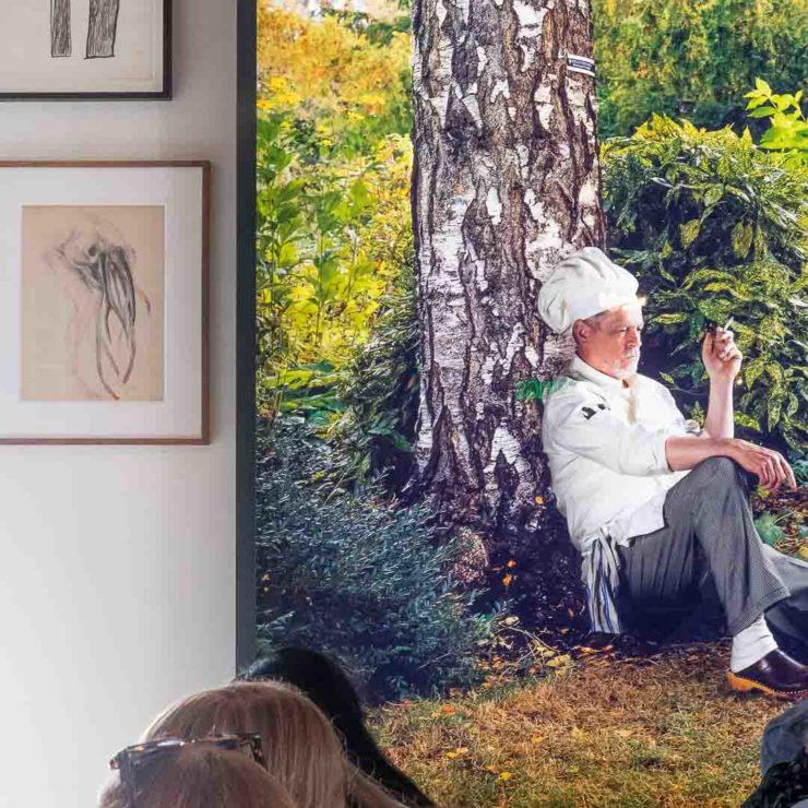 Man with chefs hat sitting under tree