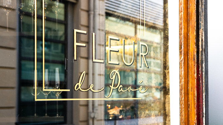 Logo of Fleur de Pave on exterior of restaurant