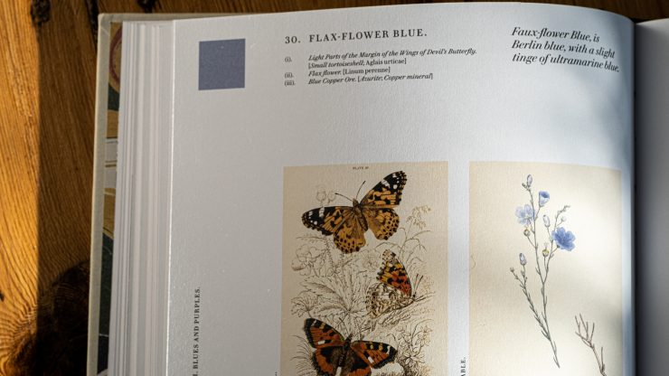 Open page of book with butterflies and flax flower