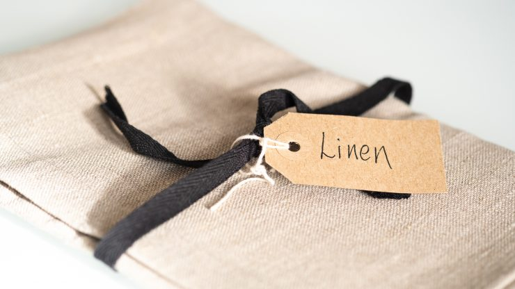 Napkin folded with black ribbon and linen tag